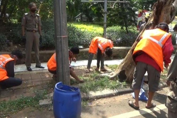 Para pelanggar PSBB di Jalan Basuki Rachmat, Jatinegara, Jakarta Timur diberi hukuman membersihkan rumput dan sampah, Rabu (3/6/2020).