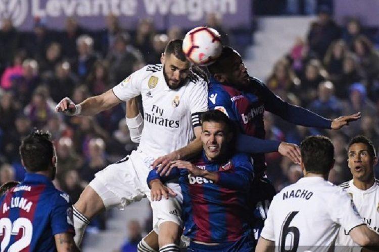 Striker Real Madrid Karim Benzema menyundul bola melawan penyerang Levante, Moses Simon, pada laga pekan ke-25 La Liga Spanyol, 24 Februari 2019.