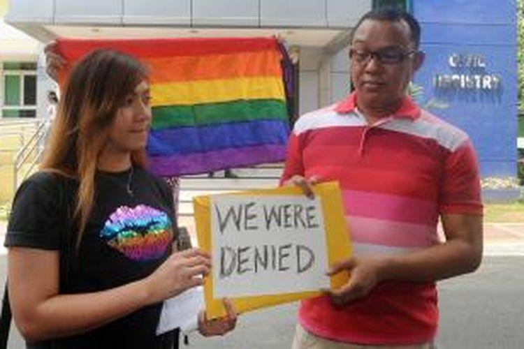 Maria Arlyn Ibanez (33) yang didampingi seorang kawannya membentangkan spanduk dan bendera warna pelangi setelah permohonanannya mendaftarkan pernikahannya dengan sang pasangan ditolak pemerintah Filipina.