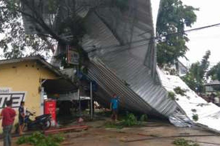 Atap berukuran raksasa yang terbang dan tersangkut di pohon akibat terbawa angin puting beliung di Jalan Gusti Hamzah, Pontianak (30/8/2016)