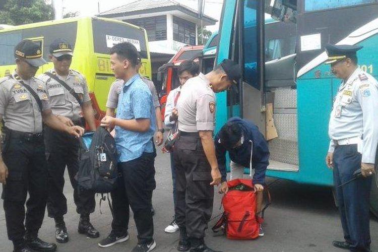 Petugas gabungan memeriksa barang bawaan penumpang bus luar kota yang tiba di Terminal Kalideres, Jakarta Barat.