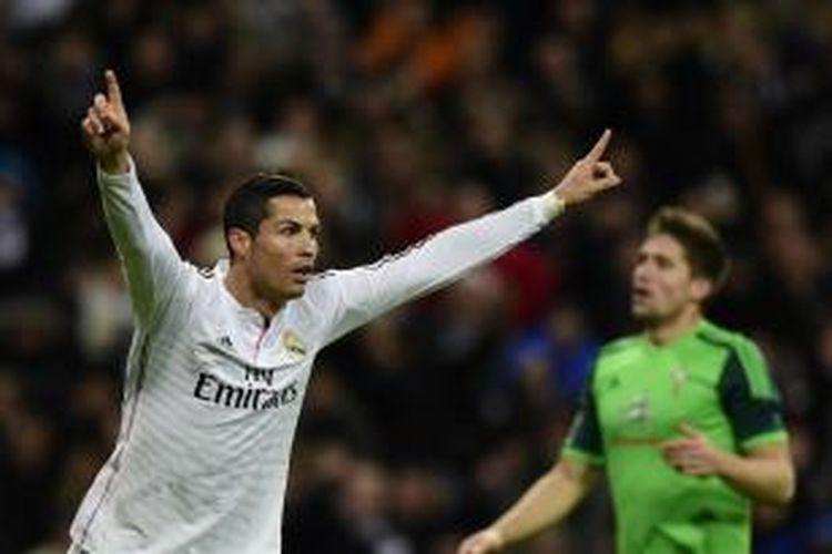 Penyerang Real Madrid, Cristiano Ronaldo, melakukan selebrasi setelah mencetak gol ke gawang Celta Vigo dalam lanjutan Primera Division di Santiago Bernabeu, Sabtu (6/12/2014).