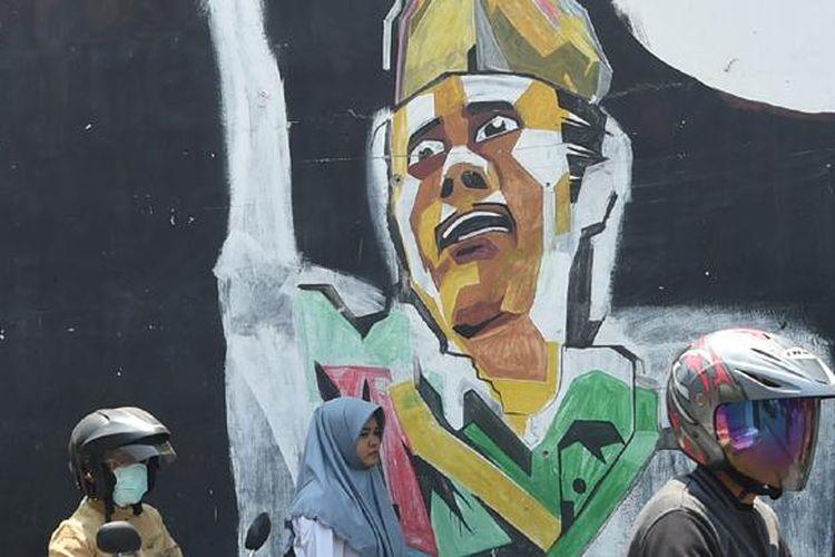 Pengendara melintasi mural bergambar Bung Tomo di Kecamatan Waru, Sidoarjo, Jawa Timur, Selasa (3/11/15). Bung Tomo menjadi ikon perlawanan arek-arek Suroboyo dalam pertempuran 10 Nomber 1945 yang kemudian dikenang sebagai Hari Pahlawan.