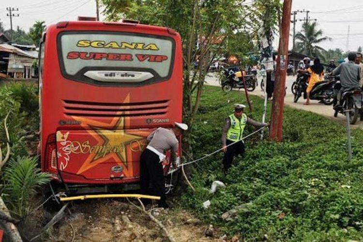 Polisi sedang memasang garis pengaman di lokasi kecelakaan bus Simpati Star di Desa Buket Pala, Kecamatan Idi Rayeuk, Aceh Timur, Minggu (30/10/2016)