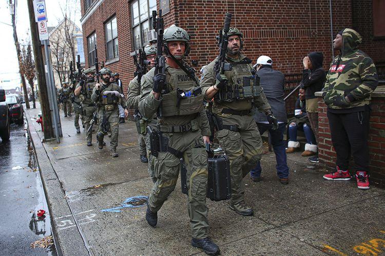 Petugas kepolisian mendatangi lokasi terjadinya penembakan di Jersey City, New Jersey, AS, Selasa (10/12/2019) waktu setempat. Dilaporkan setidaknya enam orang tewas dalam baku tembak hebat tersebut, dengan seorang polisi dan dua orang yang diyakini sebagai pelaku penembakan masuk dalam daftar korban meninggal.