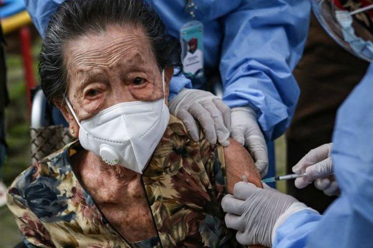 Lansia berusia 102 tahun, Inna Wati yang menerima suntikan vaksin COVID-19 di Puskesmas Poris Plawad, Kota Tangerang, Banten, Minggu (11/04).
