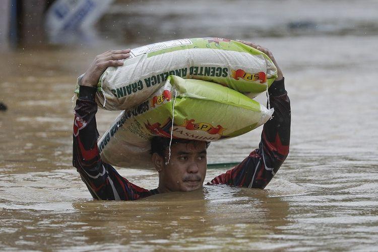 Seorang pria membawa karung beras di tengah air banjir yang terus meningkat di Marikina, Filipina akibat Topan Vamco pada Kamis, 12 November 2020.