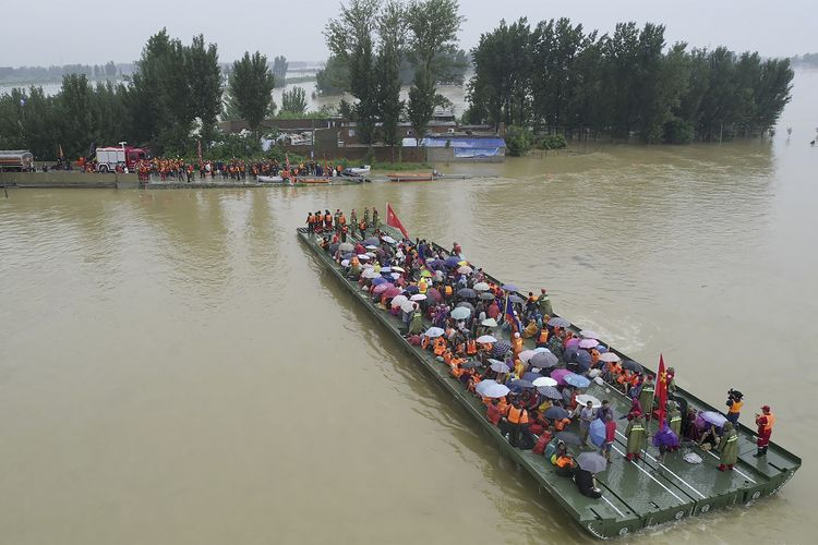 Tim penyelamat menggunakan jembatan rakit bermotor untuk mengevakuasi warga terdampak banjir China di Xinxiang, provinsi Henan, Jumat (23/7/2021). Jumlah korban tewas akibat banjir parah ini terus meningkat di kota Zhengzhou, menurut laporan media pemerintah.