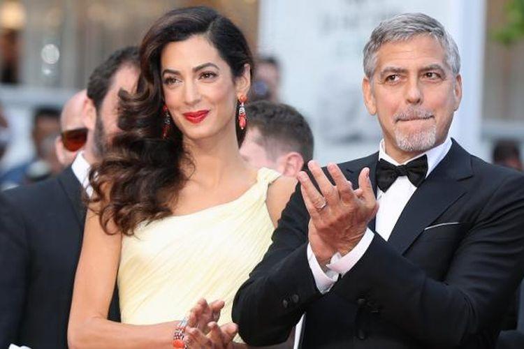 Pasangan George dan Amal Clooney menghadiri pemutaran film Money Monster di Festival Film Cannes di Perancis, pada 12 Mei 2016. Sejumlah sumber yang dekat dengan pasangan itu mengungkat bahwa Amal sedang hamil anak kembar.