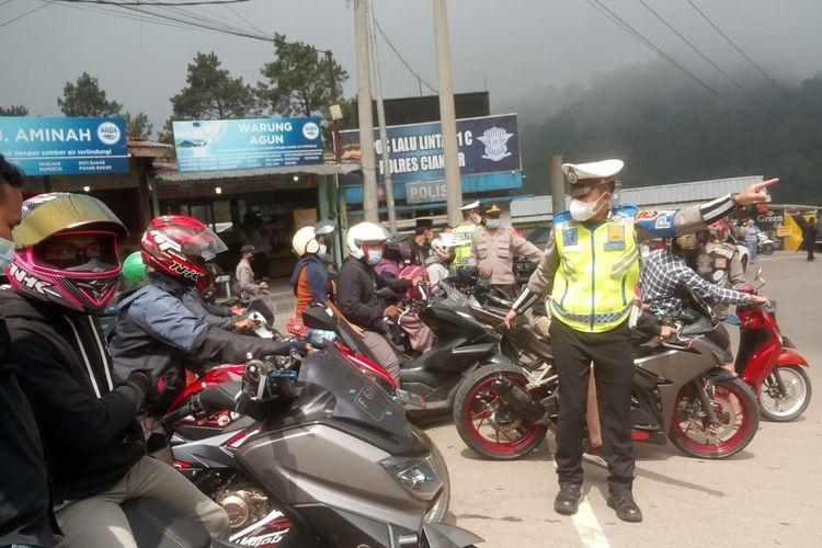 Polisi memutar balik sejumlah kendaraan di jalur Puncak perbatasam Cianjur-Bogor, Minggu (16/5/2021). Penyekatan dilakukan untuk mencegah lonjakan pengunjung wisata di Cianjur.
