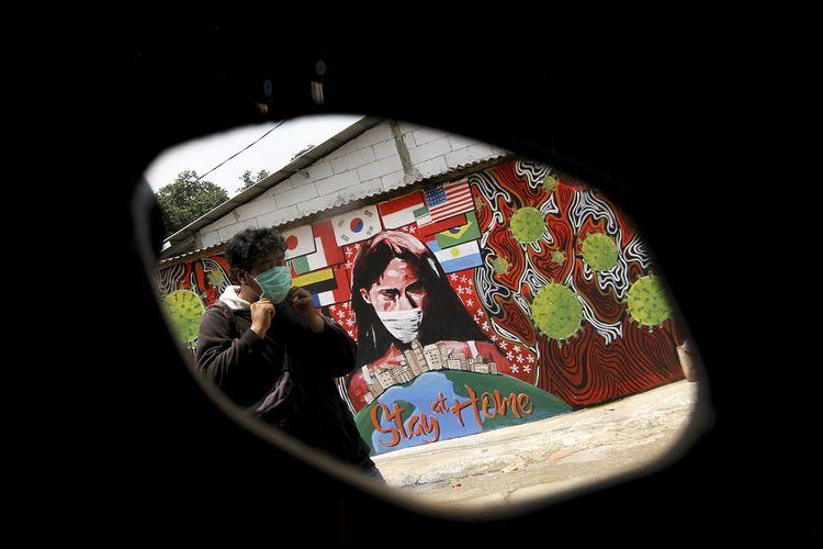 Seorang Warga melintas di depan mural bertuliskan Stay At Home di Cipayung, Depok, Jawa Barat, Selasa (14/4/2020). Pemerintah Kota Depok akan menerapkan Pembatasan Sosial Berskala Besar (PSBB) mulai Rabu (15/4) sebagai upaya memutus rantai penyebaran virus corona COVID-19. ANTARA FOTO/Asprilla Dwi Adha/hp.