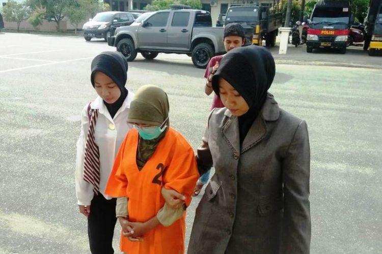 Polisi wanita menggiring N, tersangka yang diduga mencabuli lima anak pria dan wanita di Mapolres Aceh Utara, Jumat (1/2/2019)