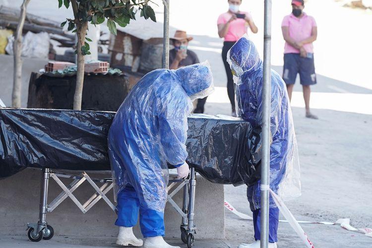 Petugas dari rumah pemakaman mengurus sebuah peti dengan jenazah seorang pria yang ditemukan di jalanan, di tengah menyebarnya Covid-19 di Cochabamba, Bolivia, pada 5 Juli 2020.