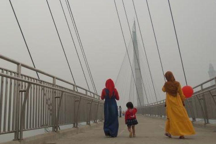 Warga Jambi tengah berjala  di Jembatan Gantung Titian Arasy, Kota Jambi, salah satu obyek wisata di Sungai Batanghari, Selasa (27/10/2015).