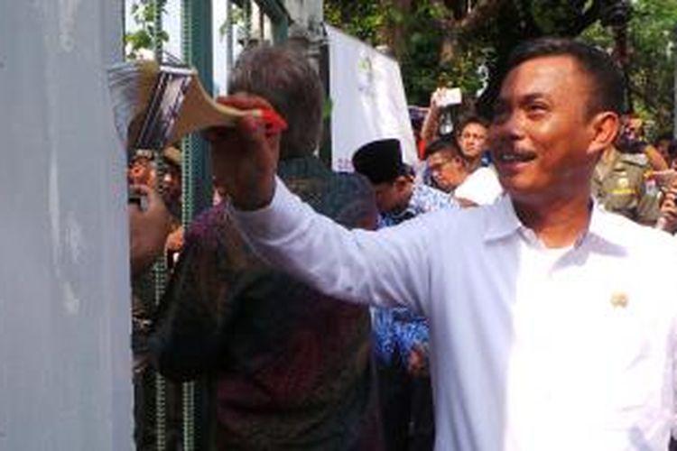 Ketua DPRD DKI Prasetio Edi Marsudi mengecat pagar Monas, Selasa (10/11/2015).