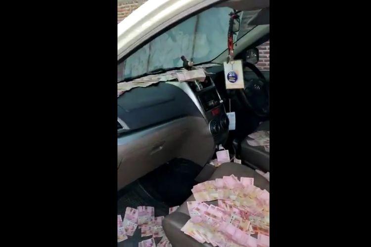 Tangkapan layar video yang menayangkan uang berserakan di dalam mobil salah satu pendukung paslon di Pilkada Kabupaten Mojokerto, Jawa Timur.