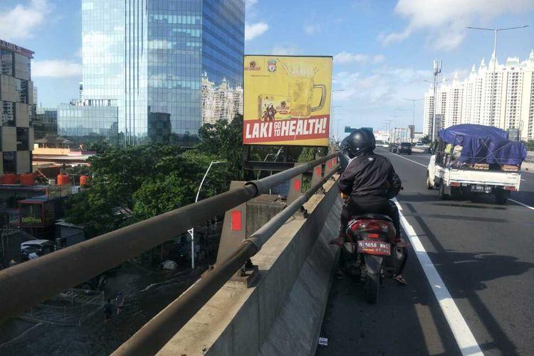 Pengendara sepeda motor masuk Tol Wiyoto Wiyono demi menghindari banjir di Jalan Yos Sudarso, Jakarta Utara, Minggu (23/2/2020)