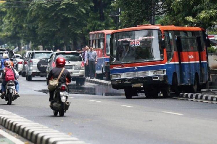 Bus metromini jurusan Blok M - Fatmawati - Pondok Labu melompati separator dan melawan arus untuk mendahului bus lainnya di jalan Melawai, Jakarta Selatan, Senin (7/12). Prilaku ugal-ugalan supir bus di jalan tidak hanya membahayakan keselamatan penumpang tetapi juga pengguna jalan lainnya.   Kompas/Priyombodo (PRI) 07-12-2015