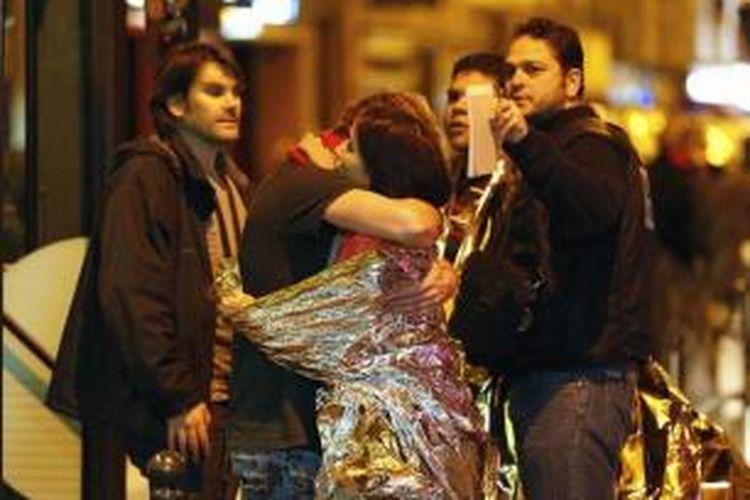 Warga berpelukan setelah dievakuasi menggunakan bis, dekat dengan gedung konser Bataclan di pusat kota Paris, 14 November 2015. Lebih dari 100 orang tewas dalam aksi penembakan dan bom yang dilakukan oleh teroris pada 13 November malam.