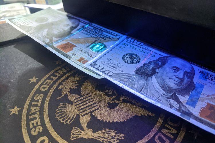 Perbandingan dollar asli dan dollar palsu yang hendak diedarkan di Jakarta Utara. Kiri dollar palsu, kanan dollar asli.