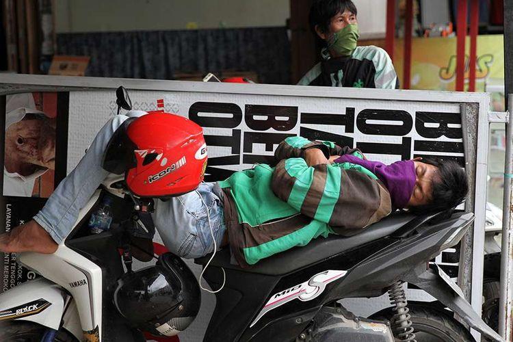 Pengemudi ojek daring tertidur di atas sepeda motornya akibat sepinya orderan di Kendari, Sulawesi Tenggara, Rabu (8/4/2020). Sejak imbauan pemerintah untuk melakukan jaga jarak fisik mengantisipasi penyebaran wabah virus COVID-19, pendapatan para pengemudi ojek daring turun drastis, menjadi tidak lebih Rp 75 ribu dibandingkan sebelum wabah yang dapat mencapai Rp 250 ribu per harinya.