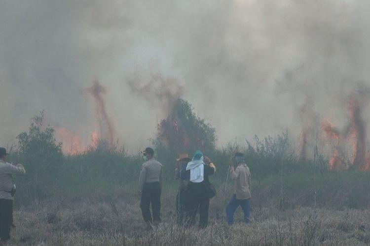 Aparat polisi dan warga memantau api kebakaran lahan yang mulai mendekat ke kebun warga di Muaraenim.
