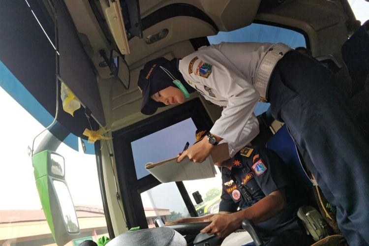 Dishub wanita tetap senyum manis di teriknya terminal Kampung Rambutan, Rabu (6/6/2018)