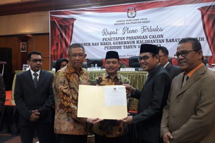 Ketua KPU Kalbar Ramdan saat menyerahkan berkas kepada gubernur Kalbar terpilih Sutarmidji dalam pleno penetapan yang digelar di Ballroom Hotel Kapuas Palace (24/7/2018)