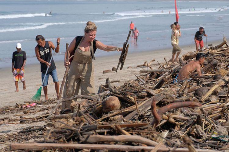 Wisatawan mancanegara turut membersihkan sampah yang terdampar akibat cuaca buruk di Pantai Kuta, Badung, Bali, Senin (11/2/2019). Hujan deras disertai angin kencang yang melanda Bali berdampak pada arus laut yang terus membawa sampah dari daerah lain dan terdampar sejumlah pantai bagian selatan Bali.
