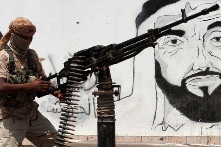 Seorang petempur Yaman beridiri di dekat mural bergambar wajah pendiri UEA, Sheikh Zayed Al Nahyan.
