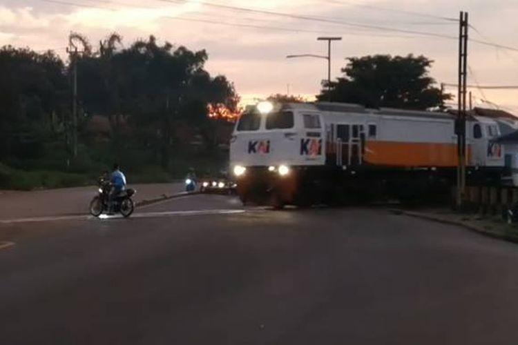 Tangkapan layar video yang menampilkan detik-detik pengendara sepeda motor nyaris tertabrak kereta api yang akan melintas.