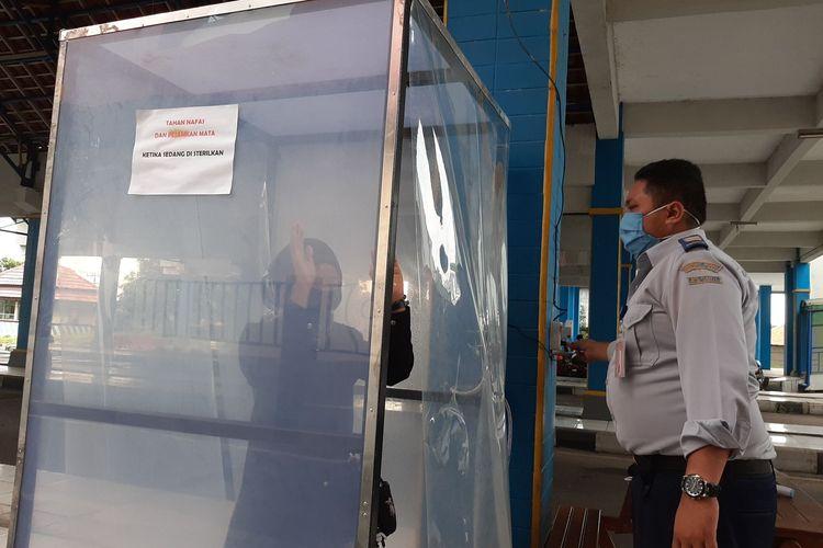 Petugas di terminal Mangkang saat melakukan proses penyemprotan di bilik disinfektan.
