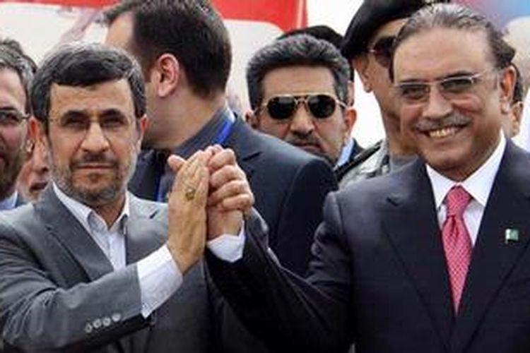 Presiden Iran, Mahmoud Ahmadinejad (kiri) menjabat erat tangan Presiden Pakistan, Asif Ali Zardari dalam sebuah upacara peresmian dimulainya pekerjaan jalur pipa gas sepanjang 780 kilometer dari Iran ke Pakistan. Peresmian ini dilakukan di kota perbatasan kedua negara Chah Bahar, Senin (11/3/2013).
