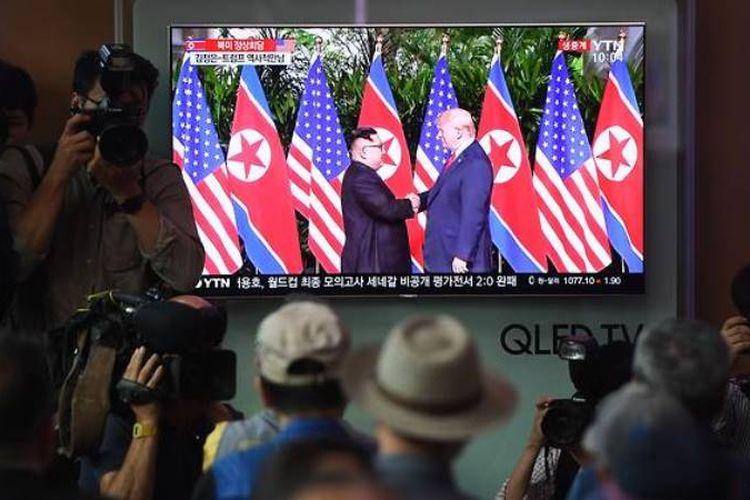 Warga berkumpul di stasiun kereta api di Seoul untuk menyaksikan siaran langsung pertemuan antara Presiden Trump dengan Kim Jong Un, Selasa (12/6/2018).
