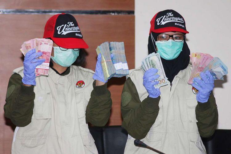 Dua penyidik KPK menunjukan barang bukti saat konferensi pers terkait operasi tangkap tangan  di Lapas Sukamiskin di Gedung KPK, Jakarta, Sabtu (21/7/2018). KPK menetapkan empat orang tersangka yaitu Kalapas Sukamiskin Wahid Husen, staf Lapas Hendri Saputra sebagai penerima suap, Fahmi Darmawansyah terpidana korupsi, dan Andri Rahmad terpidana umum sebagai pemberi suap, dengan barang bukti berupa uang senilai Rp 279.920.000 dan USD 1.410, serta satu unit mobil Mitsubishi Triton Exceed dan satu Unit Mitsubishi Pajero Sport Dakkar.