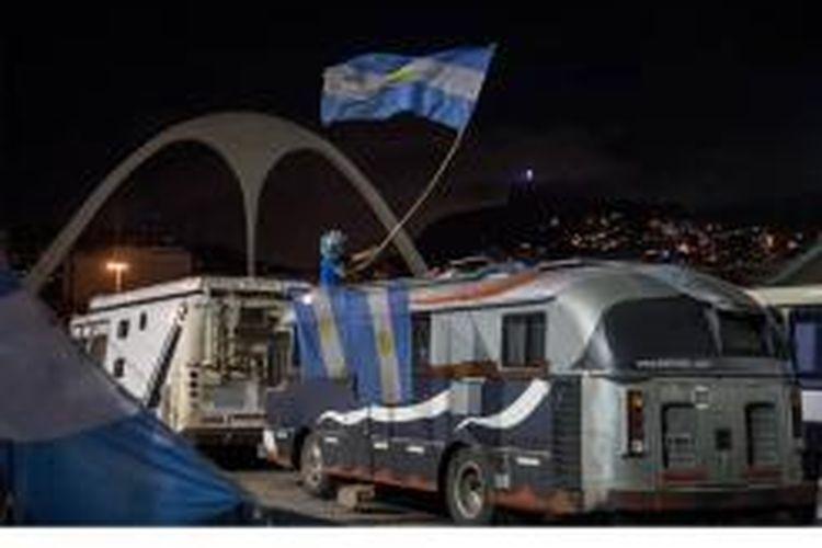 Seorang fan Argentina minum bir dan melambaikan bendera negaranya di kendaraannya di dalam Sambadrome yang dibuka untuk para pendukung memarkir dan berkemah guna menyaksikan final antara Argentina dan Jerman di ajang Piala Dunia 2014 di Rio de Janeiro, Brasil, pada 11 Juli 2014. Final akan berlansung pada 13 Juli.