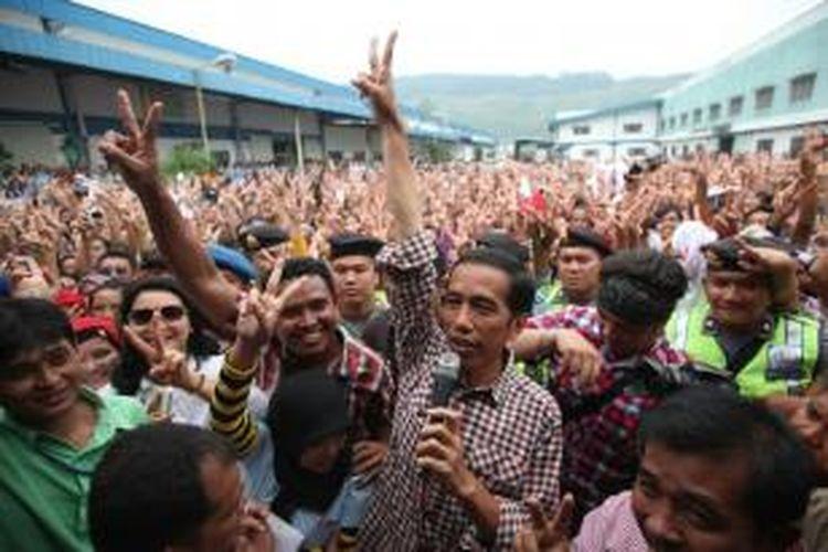 Bersama ribuan buruh, capres nomor urut 2, Joko Widodo (Jokowi), mengacungkan salam dua jari usai berorasi di halaman pabrik di Kawasan Berikat PT Daehan Global, Cibadak, Sukabumi, Jawa Barat, Rabu (2/7/2014). Dalam kesempatan itu, Jokowi mengajak buruh untuk selalu mengutamakan musyawarah dengan pengusaha untuk menyelesaikan berbagai masalah perburuhan.