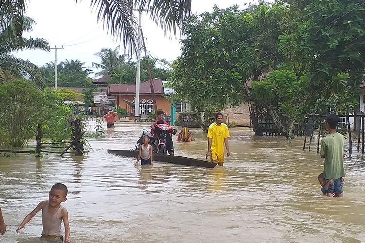 Warga mengevakuasi sepeda motor karena rumahnya digenangi banjir di Desa Sahilan Darussalam, Kecamatan Gunung Sahilan, Kabupaten Kampar, Riau, Rabu (11/12/2019).