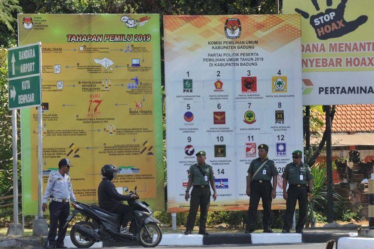 Sosialisasi Pemilu 2019 - Warga melintas di depan baliho sosialiasasi Pemilu 2019 di Jalan Ngurah Rai, Bali, Senin (8/10/2018). Sosialisasi Pemilu 2019 diharapkan tidak hanya dilakukan oleh Komisi Pemilihan Umum (KPU), namun juga peserta Pemilu 2019 agar bisa meningkatkan kesadaran masyarakat untuk menggunakan hak pilihnya dengan baik.  KOMPAS/WAWAN H PRABOWO (WAK) 08-10-2018