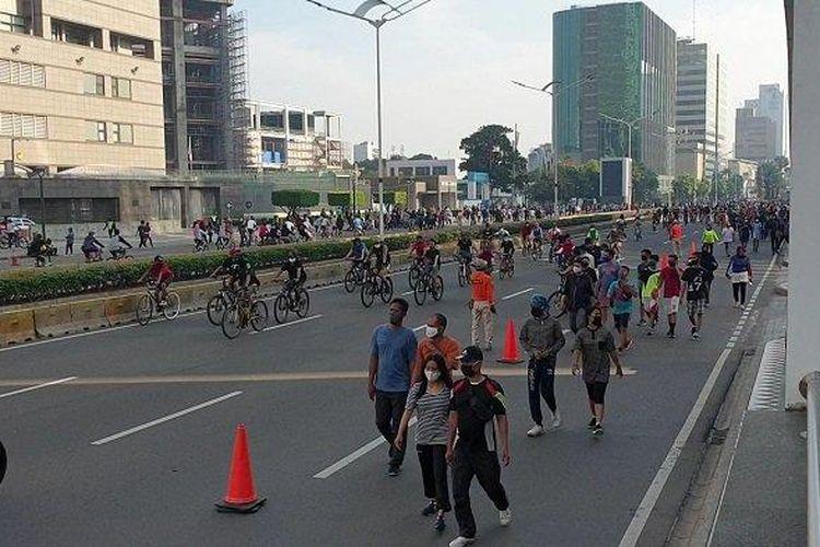 Masyarakat tampak memadati kawasan Bundaraan HI saat pelaksanaan car free day Sudirman-Thamrin, Minggu (21/6/2020).