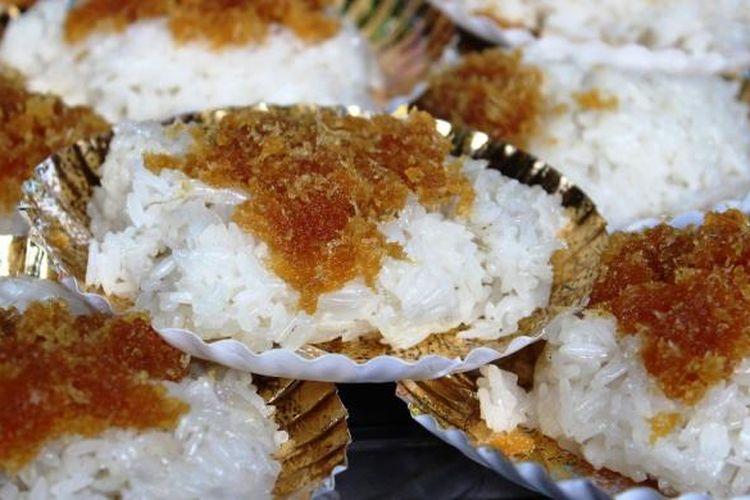 Ketan Unti, yang merupakan beras ketan putih, ditutupi dengan parutan kelapa yang sudah tercampur dengan gula merah.