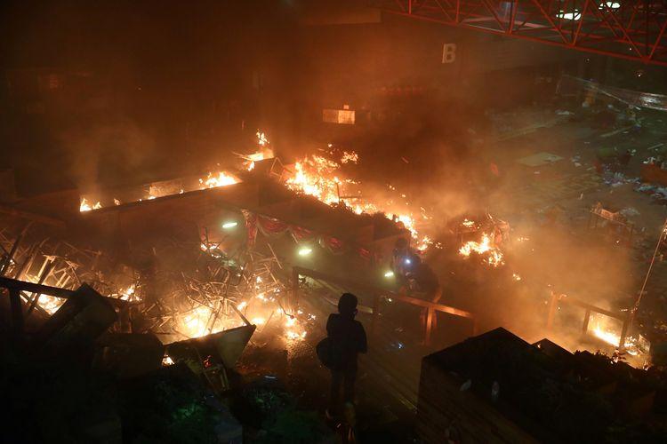 Seorang demonstran melihat kepulan api di Polytechnic University ketika terjadi bentrok dengan polisi Hong Kong pada 18 November 2019.