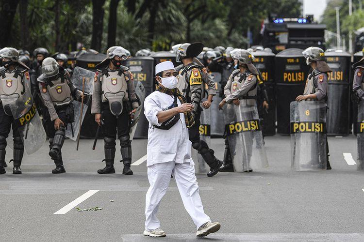 Seorang pengunjuk rasa aksi demonstrasi 1812 berjalan saat membubarkan diri, di kawasan Medan Merdeka Selatan, Jakarta, Jumat (18/12/2020). Kepolisian membubarkan paksa massa aksi demonstrasi dikarenakan angka penyebaran Covid-19 masih tinggi di wilayah Jakarta.