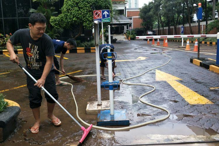 Petugas sekuriti Graha Arda membersihkan halaman gedung yang sempat terkena banjir Jalan Jalan HR Rasuna Said, Jakarta Selatan, Minggu (23/2/2020).
