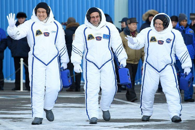Para anggota International Space Station (ISS) expedition 53/54, astronaut NASA Scott Tingle (kanan), Roscosmos kosmonaut Anton Shkaplerov (tengah), dan Norishige Kanai dari Japan Aerospace Exploration Agency (JAXA), melambaikan tangan saat seremoni pelepasan mereka di Baikonur Cosmodrome di Kazakhstan pada 17 Desember 2017. NASA astronaut Scott Tingle and crewmates Anton Shkaplerov of the Russian space agency Roscosmos and Norishege Kanai of the Japan Aerospace Exploration Agency were expected to lift off in the Soyuz MS-07 spacecraft from the Baikonur Cosmodrome. / AFP PHOTO / Kirill KUDRYAVTSEV