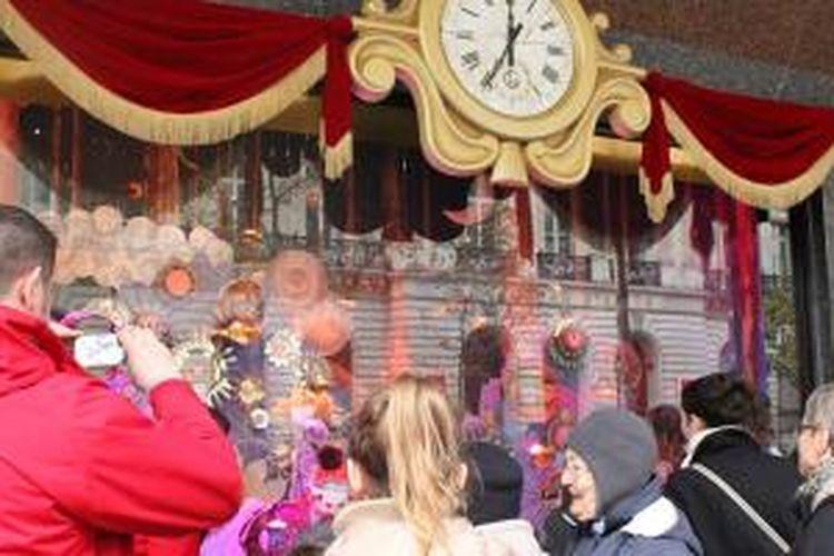 Para pengunjung yang sengaja datang untuk melihat dekorasi Natal di pertokoan Paris.