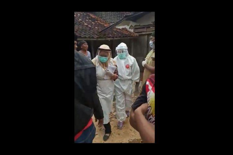 Dua petugas media berbaju hazmat meninggalkan rumah pasien Covid-19 setelah diusir oleh warga.