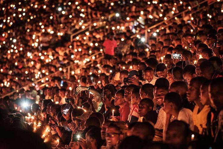 Orang-orang memegang lilin dan berdoa bersama dalam malam peringatan 25 tahun genosida Rwanda di Stadion Amahoro, Kigali, Rwanda, Minggu (7/4/2019). Seperempat abad setelah sejarah kelam itu, kini perekonomian Rwanda sudah jauh membaik dan pada 2016 ditetapkan menjadi negeri kedua terbaik di Afrika sebagai tujuan bisnis.