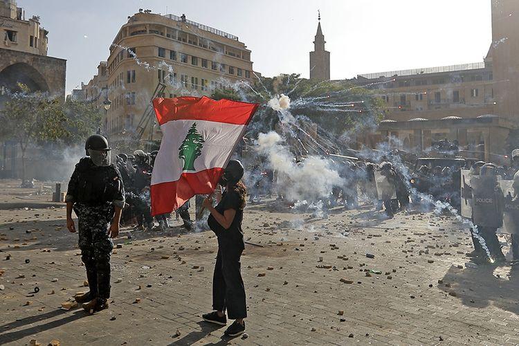 Seorang pengunjuk rasa mengibarkan bendera nasional saat demo berujung ricuh menyusul protes ledakan yang terjadi Selasa lalu, di pusat kota Beirut, Lebanon, Sabtu (8/8/2020). Unjuk rasa tersebut merupakan bentuk kemarahan warga kepada pemerintah Lebanon yang dianggap lalai, menyusul ledakan besar di Beirut pada 4 Agustus lalu yang merenggut ratusan korban jiwa.