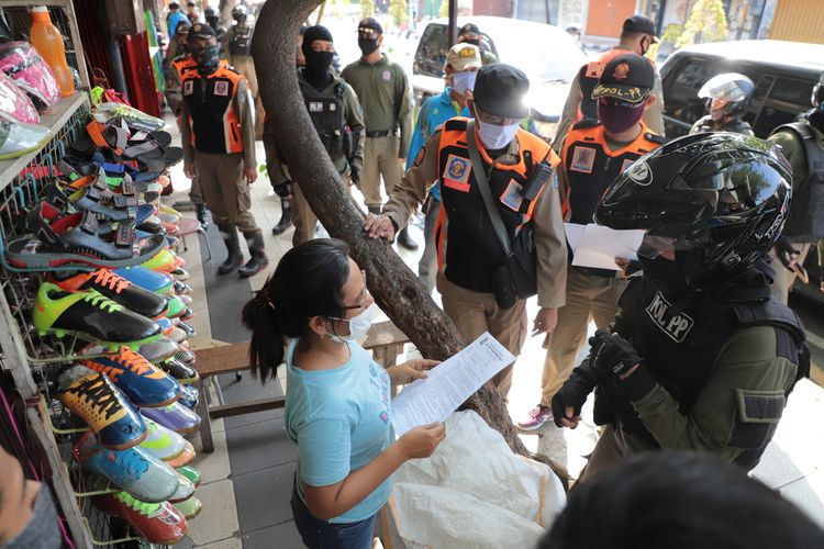 Hari keempat Pembatasan Sosial Berskala Besar (PSBB) Kota Surabaya telah memasuki masa penindakan. Satpol PP Kota Surabaya bersama kepolisian dan TNI melakukan razia dan berpatroli menyisir tempat perdagangan, warung, dan mall yang masih buka dan melanggar ketentuan PSBB, Jumat (1/5/2020).